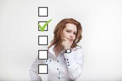 检查清单箱子的年轻女商人 灰色背景 免版税图库摄影
