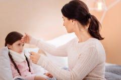 检查温度她不适的女儿的爱恋的母亲 库存照片
