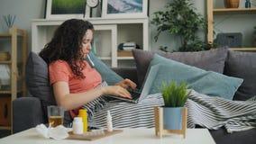检查温度的病的妇女采取药片和使用膝上型计算机浏览症状 影视素材