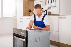 检查烤箱的技术员与数字式多用电表 免版税库存照片