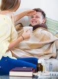 检查热病的妻子感人的丈夫前额 免版税库存图片