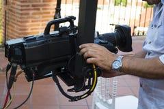 检查照相机的设备的在广播电视的摄影师 免版税库存照片