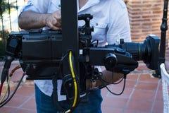 检查照相机的设备的在广播电视的摄影师 免版税图库摄影