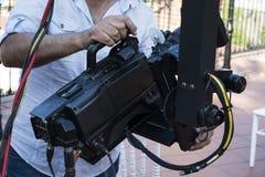 检查照相机的设备的在广播电视的摄影师 免版税库存图片