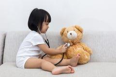 检查玩具熊的亚裔中国小女孩 图库摄影