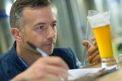检查玻璃贮藏啤酒的质量管理工作者 免版税库存照片