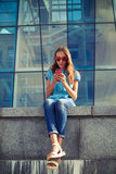 检查电子邮件的一个现代女孩通过巧妙的电话,当坐时 库存图片