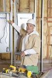 检查电表的一名成熟男性建筑工人的画象在建造场所 免版税库存图片