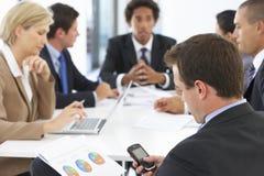 检查电话的商人在会议期间在办公室 免版税图库摄影