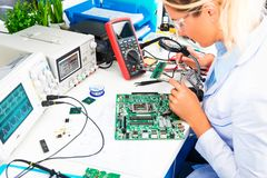 检查电路板的女性电子工程师在实验室 免版税库存照片