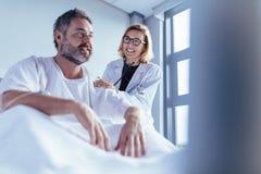 检查男性患者的女性医生在医房 免版税库存图片