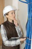 检查疏导的女性水管工用管道输送建造场所 免版税库存照片