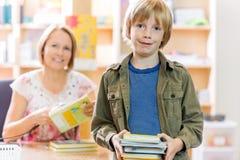 检查的男孩从图书馆预定 免版税库存图片