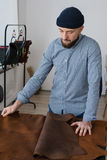 检查皮革的质量的一家小企业的业主 免版税库存照片