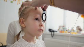 检查眼力在儿童` s眼科学-验光师诊断小女孩方面 免版税库存图片