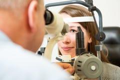 检查眼睛的验光师与裂缝 库存照片