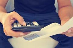 检查票据、预算或者工资单的年轻人,被过滤 免版税库存照片