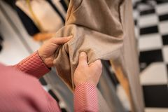 检查米黄裤子的纺织品人的特写镜头图片 免版税库存照片