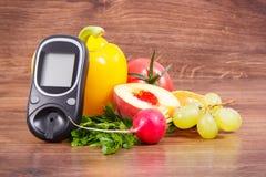 检查糖水平和果子与菜,世界糖尿病天和与的疾病概念战斗日期11月14日, glucometer 图库摄影