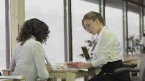 检查纸的严密的女性团队负责人与雇员,群策群力项目 影视素材