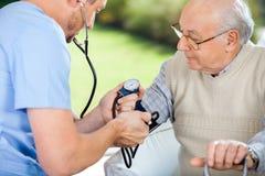 检查老人的血压男性护士 免版税库存图片
