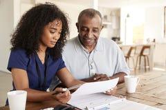 检查考试成绩的女性医疗保健工作者与一名老人在一次家庭卫生参观期间 库存照片