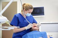 检查耐心女孩牙的女性牙医 免版税库存照片