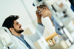 检查耐心眼力和视觉更正的验光师 图库摄影