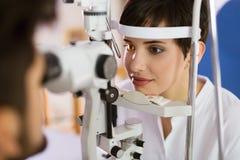检查耐心眼力和视觉更正的验光师 免版税库存图片