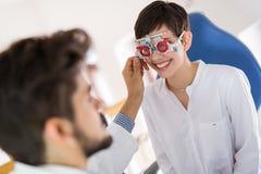 检查耐心眼力和视觉更正的验光师 免版税图库摄影