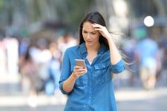 检查聪明的电话留言的担心的妇女 免版税库存照片