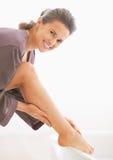 检查腿皮肤软性的妇女画象在卫生间里 免版税库存照片