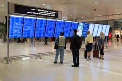 检查航行时刻表的乘客在机场 库存照片