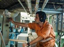 检查船` s引擎的轮机员在发动机控制室 库存照片