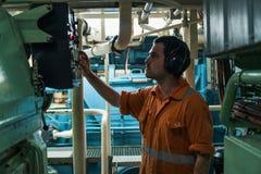 检查船` s引擎的轮机员在发动机控制室 库存图片