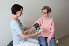 检查血压家年长妇女的女性护士 库存照片