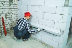 检查被供气的具体块墙壁的质量的建造者与建筑统治者 免版税库存图片