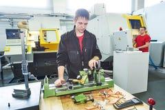 检查被处理的工具的质量的工作者 免版税库存照片