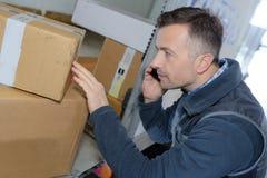检查装载的英俊的送货员谈话在电话 免版税库存照片