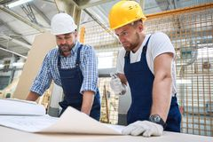 检查计划的两名建筑工人 免版税库存照片