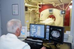 检查计算机化的轴向X线体层照相术扫描计算机辅助测试扫描的资深医生 免版税库存照片