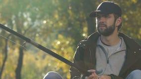 检查诱饵的乏味男性转动的钓鱼的卷轴在河,坏天,恶劣的抓住附近 股票视频