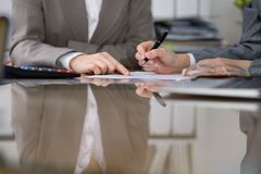 检查财政决算或计数由计算器收入的两名女性会计为报税表,手特写镜头 库存照片