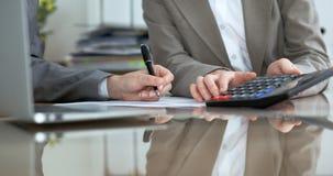 检查财政决算或计数由计算器收入的两名女性会计为报税表,手特写镜头 库存图片