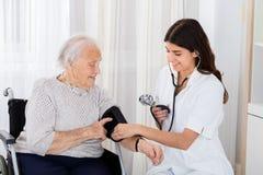 检查资深妇女的血压女性医生 库存照片