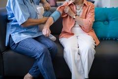 检查资深妇女血压的医生的低部分 库存图片