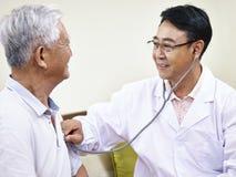 检查资深患者的亚裔医生 免版税库存照片