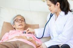 检查资深患者的家庭医疗女性医生或护士使用听诊器在医院病床或家,年轻亚裔照料者上 免版税库存图片