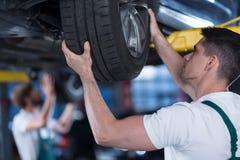 检查轮子的汽车修理师 免版税库存照片