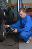 检查轮胎气压的自动服务技术员 免版税库存照片